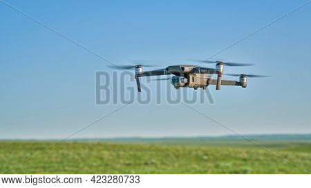 New Raymer, CO, USA - June 8, 2021:  Radio controlled DJI Mavic 2 Pro quadcopter drone is flying over green prairie.
