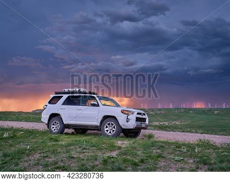 Keota CO, USA - June 7, 2021: Toyota 4Runner SUV (2016 Trail edition) in Pawnee National Grassland in northern Colorado, late spring scenery with a stormy sunset sky.