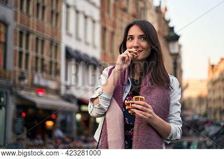Happy Girl Walk And Eat Belgian Waffles On City Street