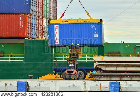 Labuan,malaysia-may 20,2021:big Containers Being Unloaded From A Huge Cargo Ship In The Port Of Labu