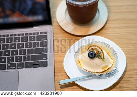 Close-up Of Ice Coffee In Cup Mug And Homemade White Orange Cake with Keyboard  Laptop Computer On