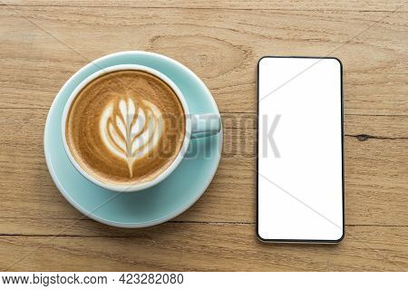 Smartphone With Empty Screen And Hot Coffee Latte With Latte Art Milk Foam In Cup Mug On Wood Desk O
