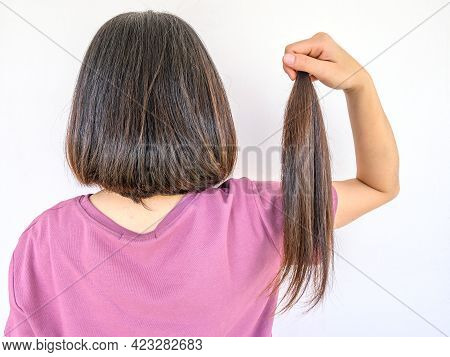 Back View Of Woman Holding A Ponytail Cutting Hair For Donation. Usable Hair Can Turn Your Long Lock