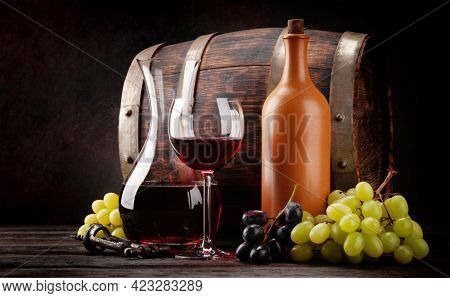 Vintage wine bottle, glass decanter, wineglass with red wine, grapes and old wooden barrel