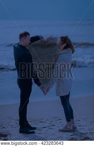 Young Couple Making Heart Shape With Arms On Sea Beach Against Dark Moonlight Tone Spring,autumn Eve