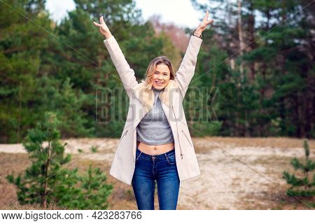 Young Beautiful Blonde Long Haired Woman Standing Front View With Raised Hands Over Green Natural Ba