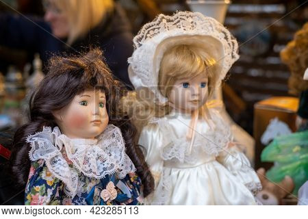 Collection of porcelain dolls in creative clothes placed on counter at local souvenir bazaar