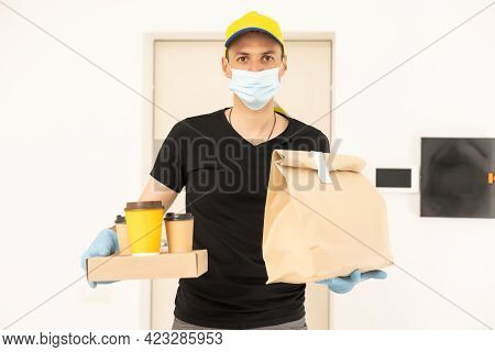 Delivery Man Holding Package To Deliver. Courier Hand Holding Brown Box Isolated On Grey Background.