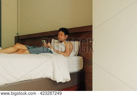 Asian Man Is Using Smartphone On The Bed In The Hotel. Concept Of Laziness And Relax.