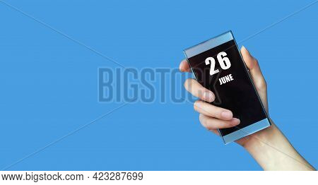 June 26. 26th Day Of The Month, Calendar Date.woman's Hand Holds Mobile Phone With Blank Screen On B