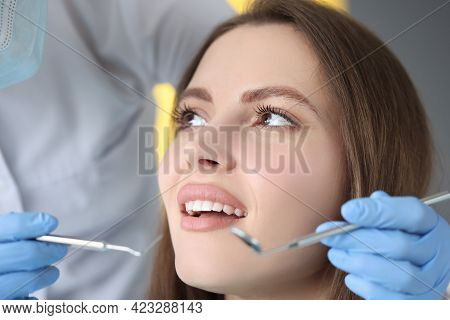 Doctor Conducts Dental Examination Of Woman Patient