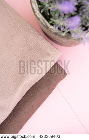 Colorful Cotton Folded Clothes Stack And Lilac Indoor Plant In A Pot. Stack Of Multicolored Clothes