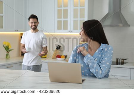 Young Woman In Pajamas Using Laptop While Her Boyfriend Bringing Coffee At Home
