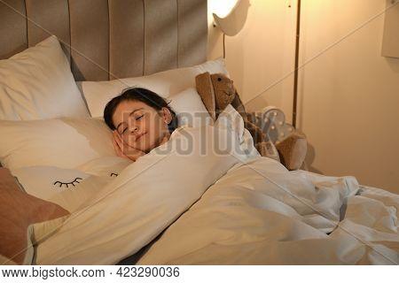 Little Girl Sleeping In Bedroom Lit By Night Lamp
