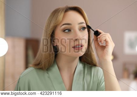 Reflection Of Beautiful Young Woman Applying Mascara In Mirror At Home