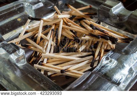 A Pile Of Burnt Matches In A Glass Ashtray. High Quality Photo