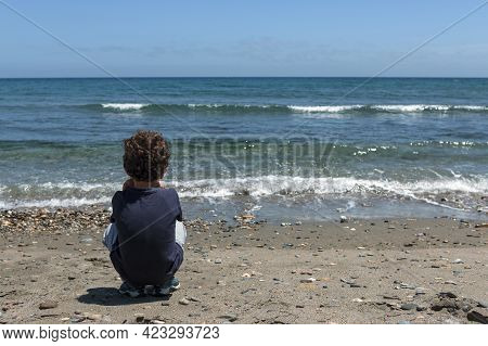 Little Boy, 4 Years Old, Caucasian, With Brown And Curly Hair, Alone On The Beach Watching The Sea I