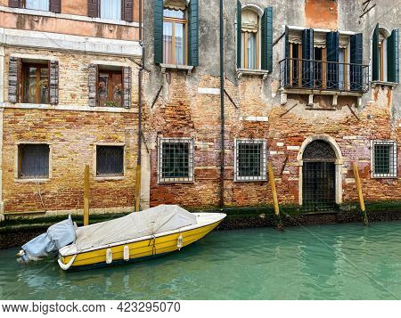 Side view of a yellow boat docking in front of a old red bricks venetian house