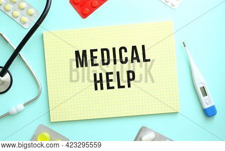 The Text Medical Help Is Written In A Yellow Notebook That Lies Next To The Stethoscope, Medicine On