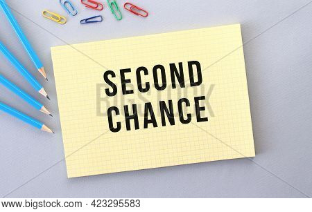Second Chance Text In Notebook On Gray Background Next To Pencils And Paper Clips. Concept.