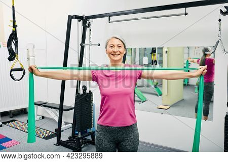 Adult Woman Doing Exercises With Resistance Bands For Recovery Of Her Hands And Shoulders After Trau