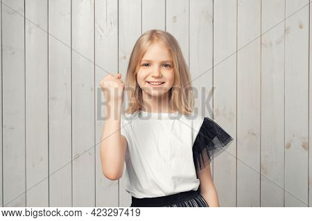 Smiling Blonde Teen Girl Celebrates Success, Achieve Goal, Say Yes And Raising Fist Up From Joy, Tri
