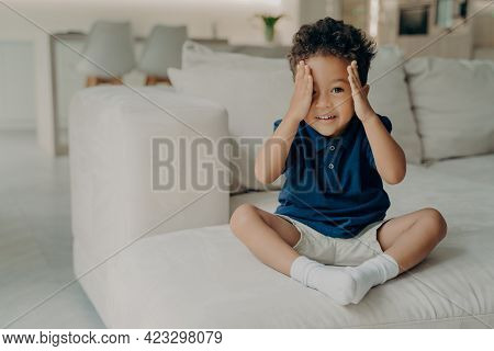 Adorable Curly Afro American Boy In Casual Wear Sitting On Comfy Big White Couch And Ready To Play,
