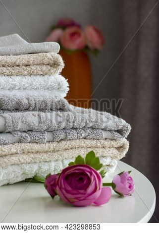 A Stack Of Terry Shower Towels On A White Table Close-up Next To Artificial Peony Flowers