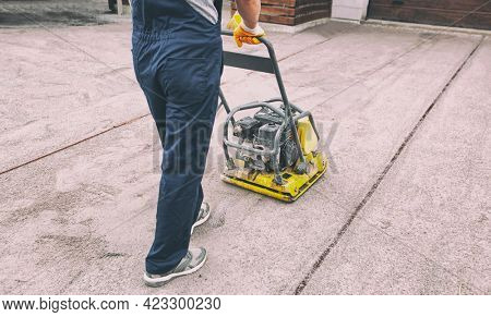 The worker tamping a gravel by the vibration plate