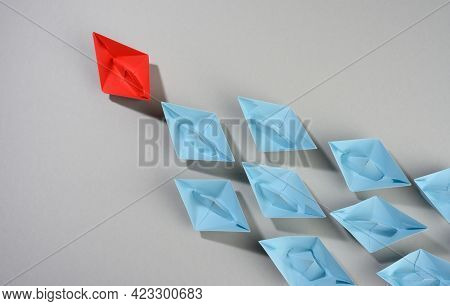 Group Of Paper Boats On A Gray Background. Concept Of A Strong Leader In A Team, Manipulation Of The