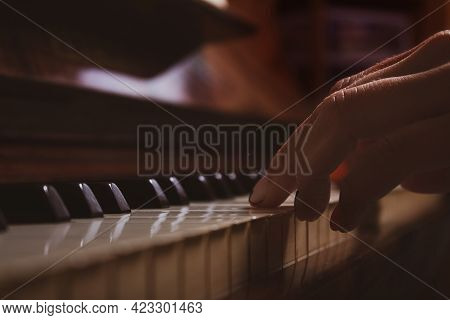 Caucasian Woman Sitting On Brown Vintage Piano And Playing. Close-up. Fingers On Piano Keys. Toned P