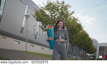 Active Woman With Fitness Mat And Water Bottle In Hands Walking In Park. Happy Lady Strolling In Sum