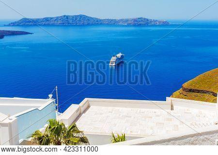 Santorini, Greece Iconic View Of White Houses, Caldera, Volcano Island And Sea Panorama With Cruise