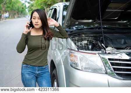 Angry Asian Woman And Using Mobile Phone Calling For Assistance After A Car Breakdown On Street. Con
