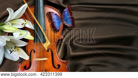 Concept Of Music. Violin With Bow, White Lily Flower And Bright Blue Morpho Butterfly On Brown Silk