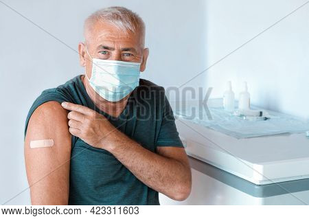 Male Senior In Face Mask After Receiving Covid-19 Vaccine. Elderly Man Feeling Good On Getting Coron