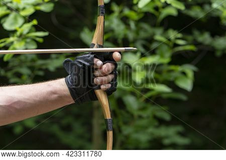 A Rough Man\'s Gloved Hand Holds A Bow And Aims An Arrow, Close-up, Selective Focus. Concept: Men\'s