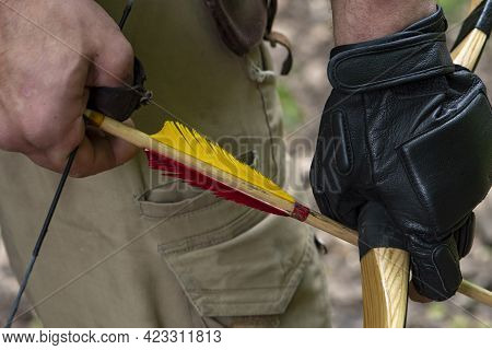 A Rough Man\\\'s Gloved Hand Holds A Bow And Aims An Arrow, Close-up, Selective Focus. Concept: Men\