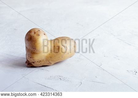 Ugly Potatoes In The Shape Of A Heart On A Gray Concrete Background. Food Waste And The Concept Of U