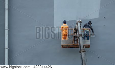 Two Painters In A Construction Cradle Paint The Facade Of A Building