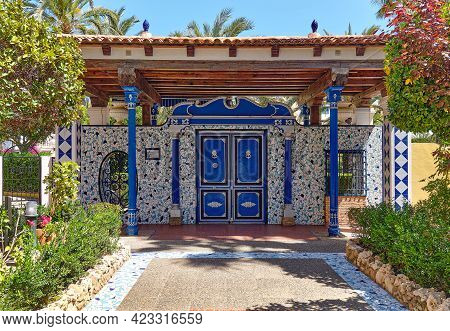 Pathway Lined With Green Lush Plants Leading To The Classic Decorative Ceramic Azulejo Tiled Doorway
