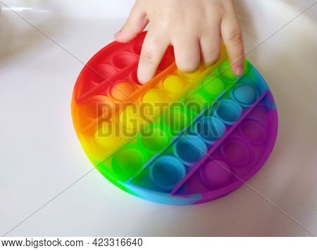 The Pop It Is A Stress-reducing Toy. A Small Child Is Playing. Small Fingers Press On Points. A Game