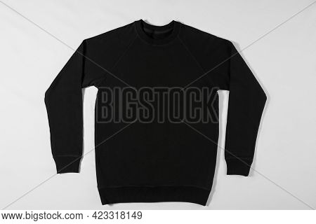 Black Raglan Lying On A White Background In The Studio. Classic Clothing Concept. Blank Sweater With