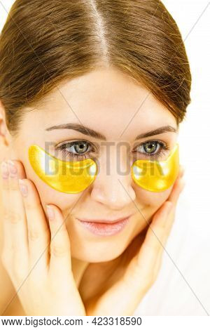 Young Woman Applying Golden Collagen Patches Under Eyes. Mask Removing Wrinkles And Dark Circles. Gi