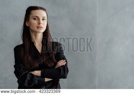 Business Portrait Of Young Confident Woman Looking At Camera, Crossed Hand On Chest, Standing Agains
