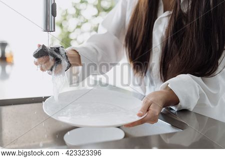 Cropped View Of Young Woman Washing Plate And Squeeze Sponge With Organic Detergent Over Sink. House