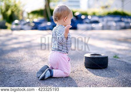 Child Kneels Near A Car Rim In A Parking Lot