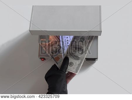 A Hand In A Black Glove Holds Three Banknotes For Verification. The Ultraviolet Lamp Of The Currency