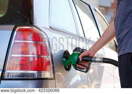 The Driver Has Inserted A Gas Station Gun Into The Tank, Refueling The Car With Gasoline At The Gas