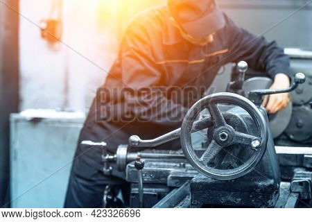 Unrecognizable Blurred Worker In Uniform At Work With Metalworking Machine.